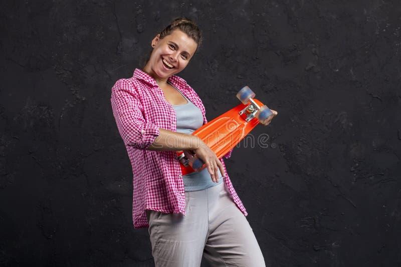 Retrato de uma moça bonita elegante com um skate nas mãos foto de stock