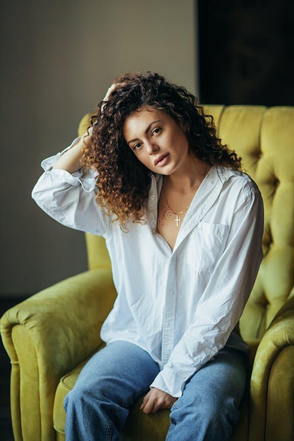 Retrato de uma moça bonita em um estúdio escuro Cabelo Curly imagem de stock