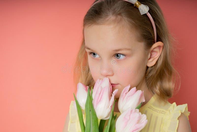 Retrato de uma moça bonita no vestido que guarda o ramalhete grande das tulipas isoladas sobre o fundo cor-de-rosa imagens de stock royalty free