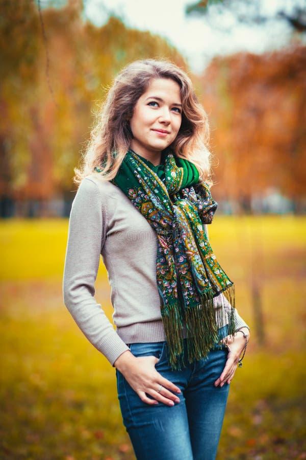 Retrato de uma moça com o lenço de pescoço verde no parque do outono do fundo fotos de stock