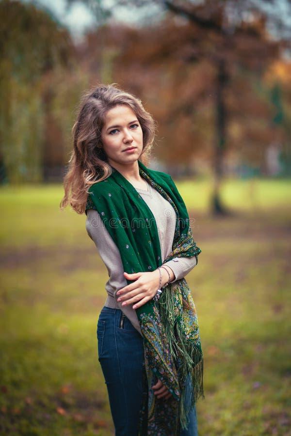 Retrato de uma moça com o lenço verde no parque do outono do fundo imagem de stock royalty free