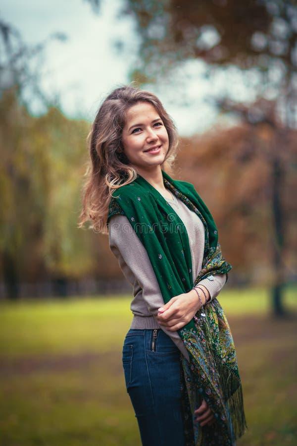 Retrato de uma moça com o lenço verde no parque do outono do fundo imagens de stock royalty free