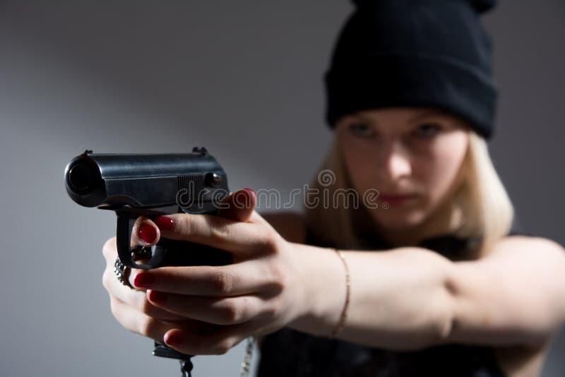 Retrato de uma moça com uma arma em sua mão foto de stock