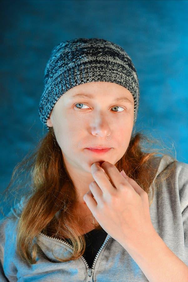 Retrato de uma moça em um chapéu feito malha sem composição, close-up em um fundo azul A beleza natural de uma mulher foto de stock