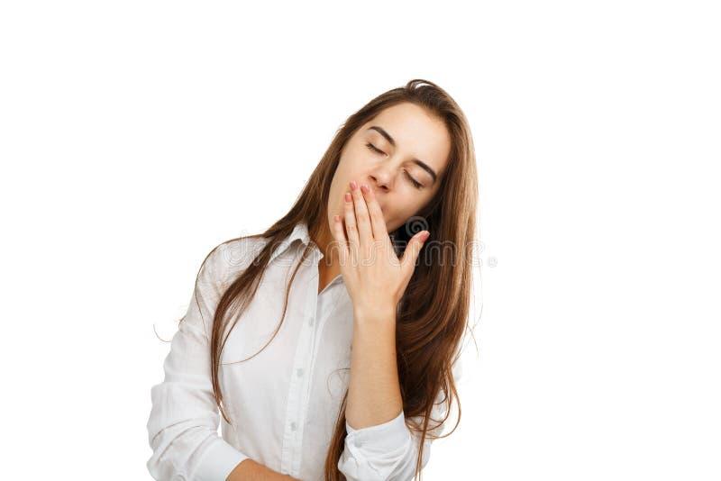Retrato de uma moça em um fundo branco que boceje imagem de stock royalty free
