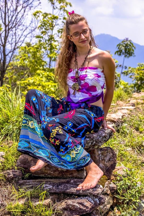 Retrato de uma mo?a feliz e de uma saia maxi floral vestida com parte superior, espet?culos situa??o no fundo da rocha e do c?u a foto de stock royalty free
