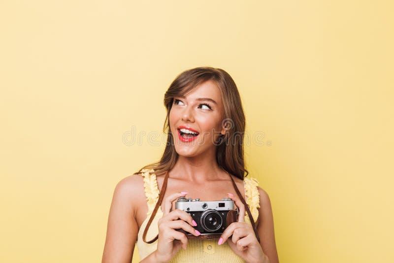 Retrato de uma moça feliz que guarda a câmera da foto fotografia de stock