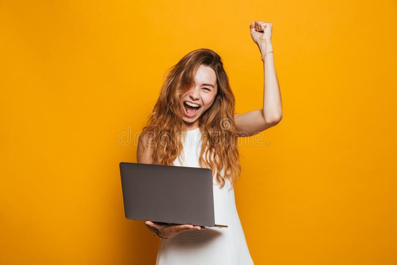 Retrato de uma moça feliz que guarda o laptop imagens de stock