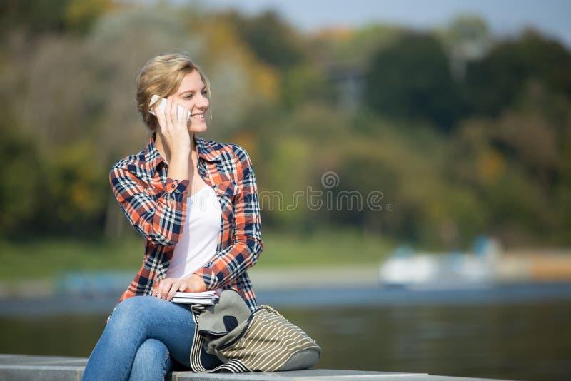 Retrato de uma moça na ponte, falando no telefone fotografia de stock