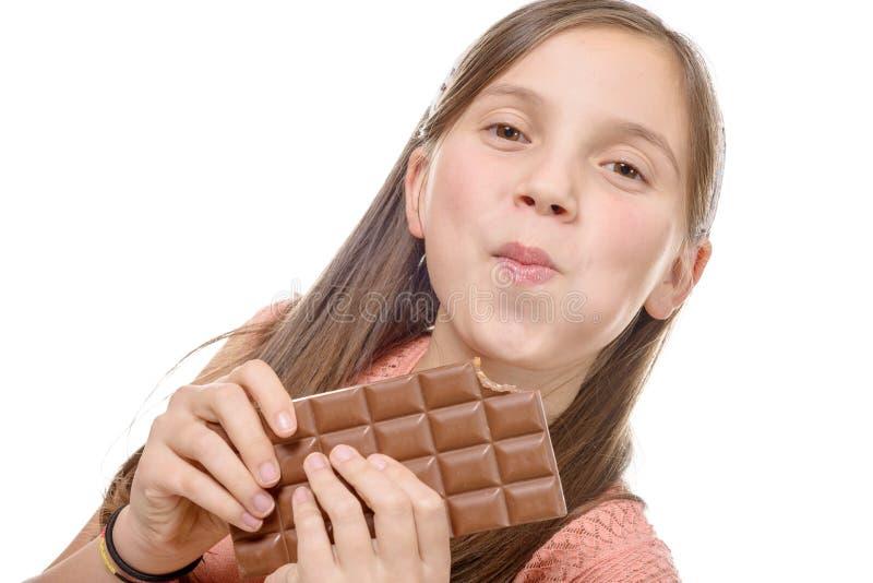 Retrato de uma moça que come uma barra de chocolate isolada no whit foto de stock royalty free