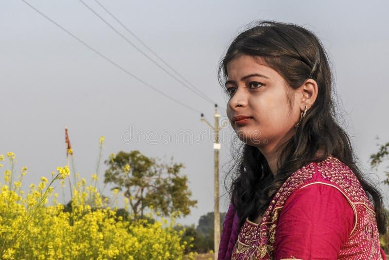 Retrato de uma moça que pertence ao bengali ocidental da Índia que senta-se em um campo da semente de mostarda, vestindo o vestid imagens de stock royalty free