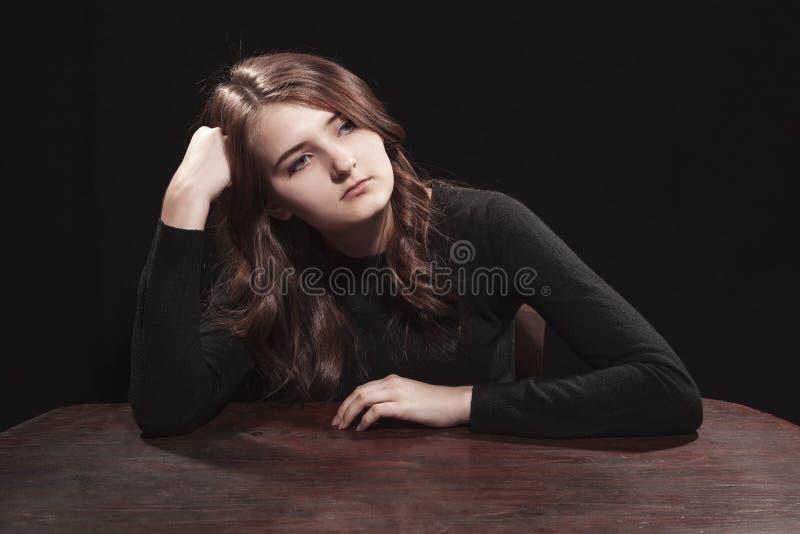 Retrato de uma moça que senta-se na tabela fotos de stock royalty free