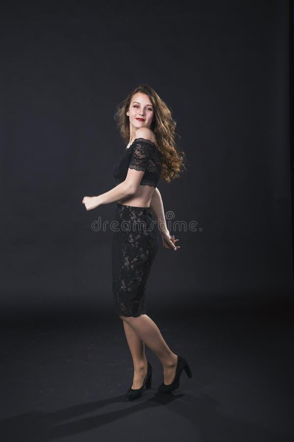 Retrato de uma moça de sorriso em um vestido do laço em um fundo preto imagens de stock royalty free