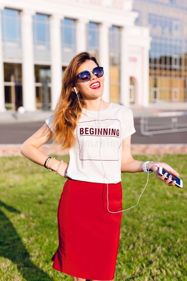Retrato de uma moça de sorriso ereta que guarda um smartphone e que escuta a música nos fones de ouvido A menina veste um t branc imagem de stock royalty free