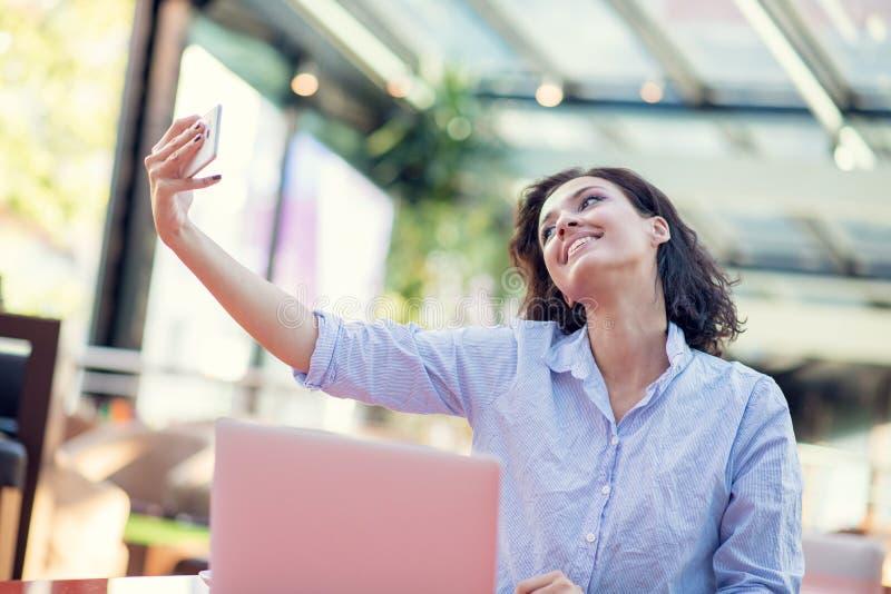 Retrato de uma mo?a brincalh?o que toma o selfie com telefone celular ao sentar-se com laptop em um caf? fora foto de stock royalty free
