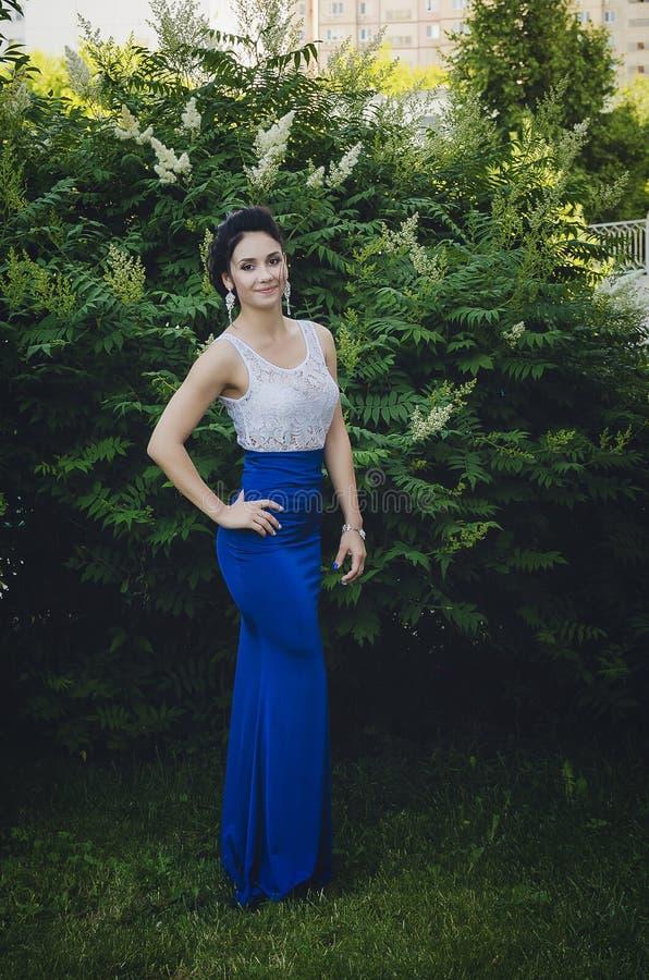 Retrato de uma morena bonita em uma blusa branca e em uma saia azul no crescimento completo imagem de stock royalty free