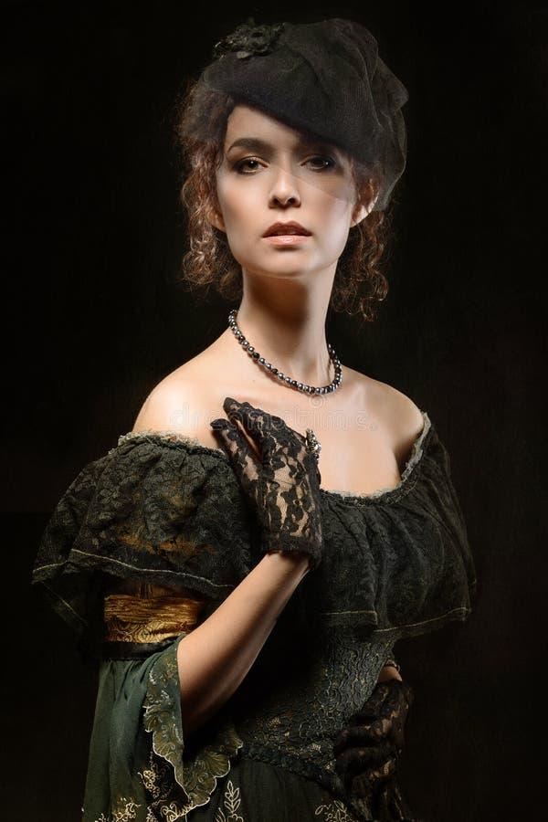 Retrato de uma morena em um chapéu e em luvas fotografia de stock