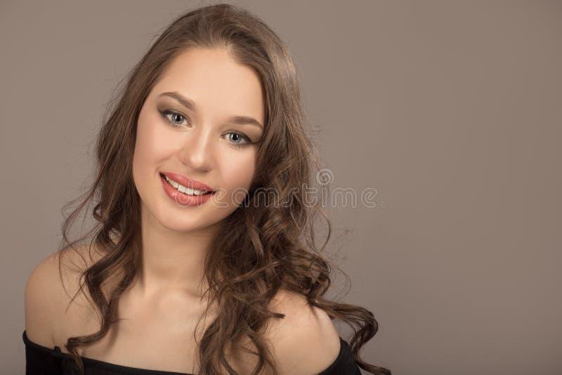 Retrato de uma morena nova bonita com cabelo ondulado longo fotografia de stock