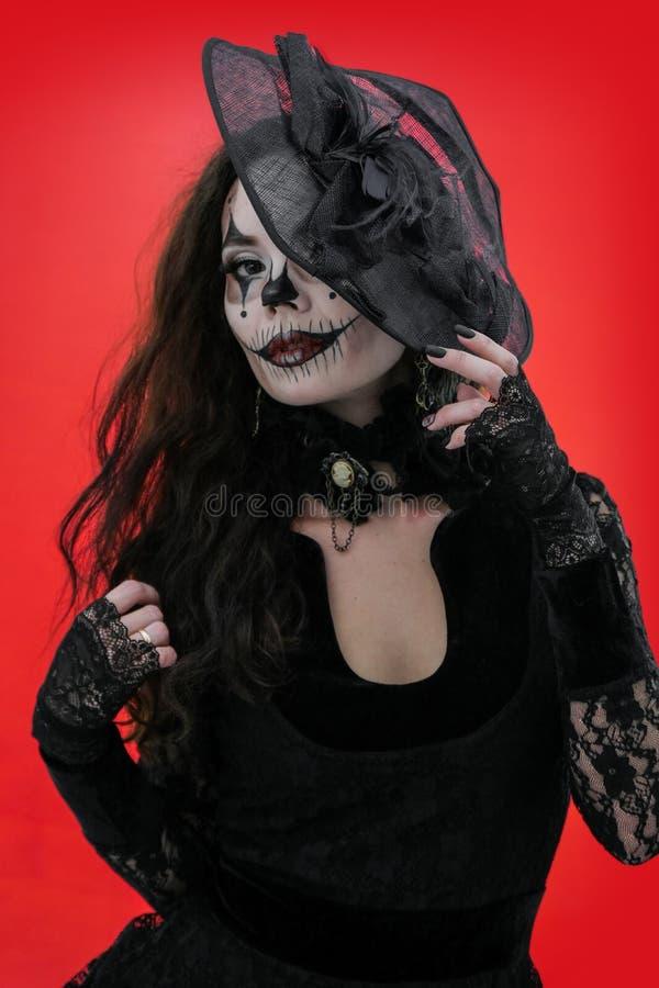 Retrato de uma morena nova com composição ao estilo de Dia das Bruxas na roupa e no chapéu pretos Menina horrívea com boca assust fotos de stock
