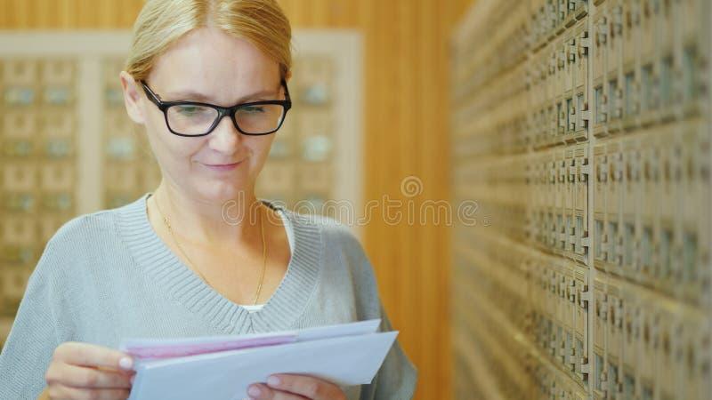 Retrato de uma mulher à moda nova com um pacote de letras em suas mãos na estação de correios foto de stock