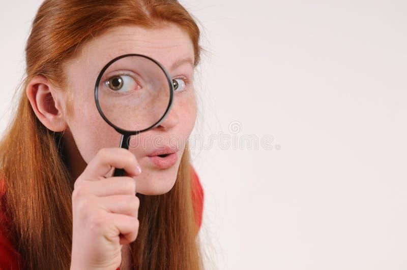 Retrato de uma mulher adolescente do cabelo vermelho novo que olha a câmera através de uma lupa foto de stock