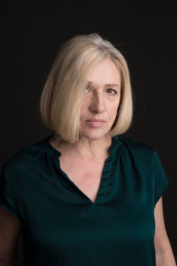 Retrato de uma mulher adulta loira isolada num estúdio sobre fundo escuro fotografia de stock royalty free