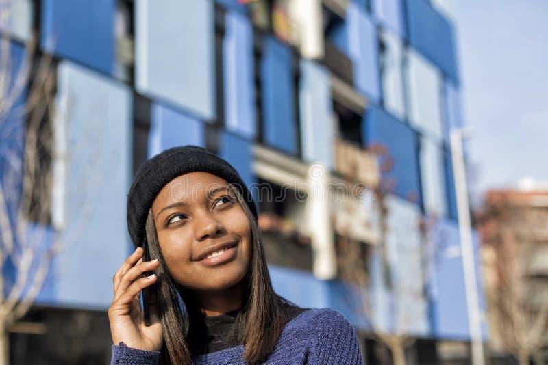 Retrato de uma mulher africana nova alegre que está fora e que faz um telefonema ao olhar afastado imagens de stock royalty free
