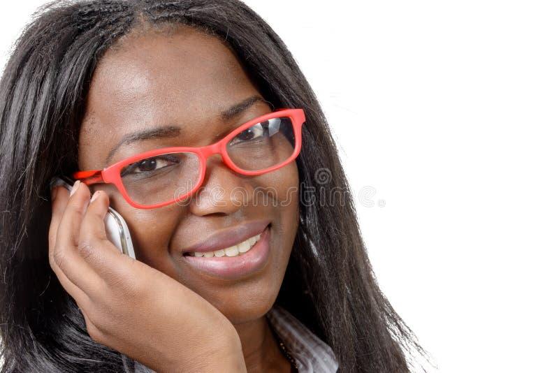 Retrato de uma mulher africana nova bonita que fala no phon da pilha foto de stock