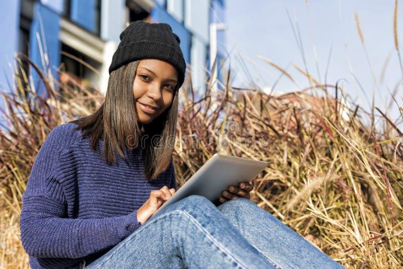 Retrato de uma mulher africana de sorriso nova bonita que usa o computador do PC da tabuleta que senta-se na cidade em um dia ens fotografia de stock royalty free