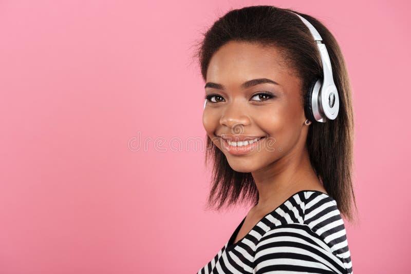 Retrato de uma mulher afro-americana feliz de sorriso nos fones de ouvido fotografia de stock