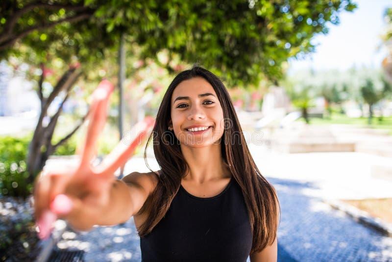 Retrato de uma mulher alegre A vitória ou a paz bonita da exibição da mulher assinam dentro a rua do verão fotos de stock