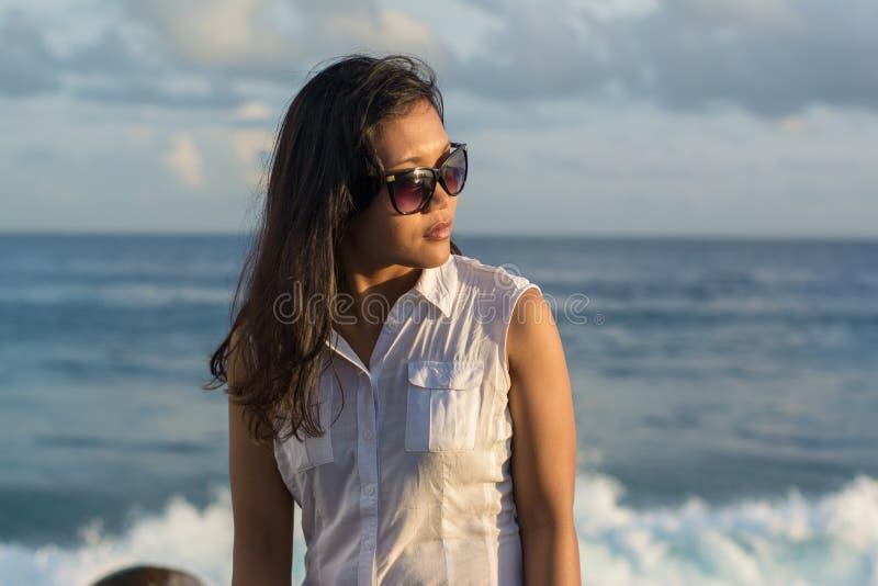 Retrato de uma mulher asiática bonita nova nos óculos de sol que examinam um lado com o oceano o fundo imagens de stock