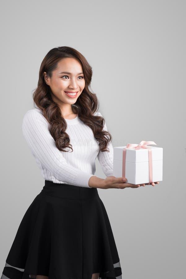 Retrato de uma mulher asiática bonita de sorriso que guarda o isolat da caixa de presente foto de stock royalty free