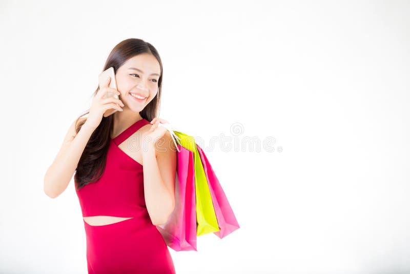 retrato de uma mulher asiática entusiasmado feliz no telefone do vestido vermelho e no saco de compras de fala estando guardar foto de stock royalty free