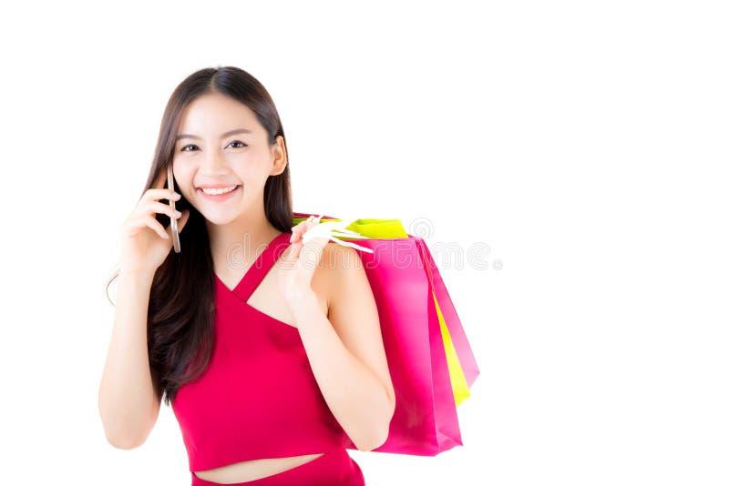 Retrato de uma mulher asiática entusiasmado feliz no telefone de fala estando e em guardar do vestido vermelho sacos de compras c fotografia de stock