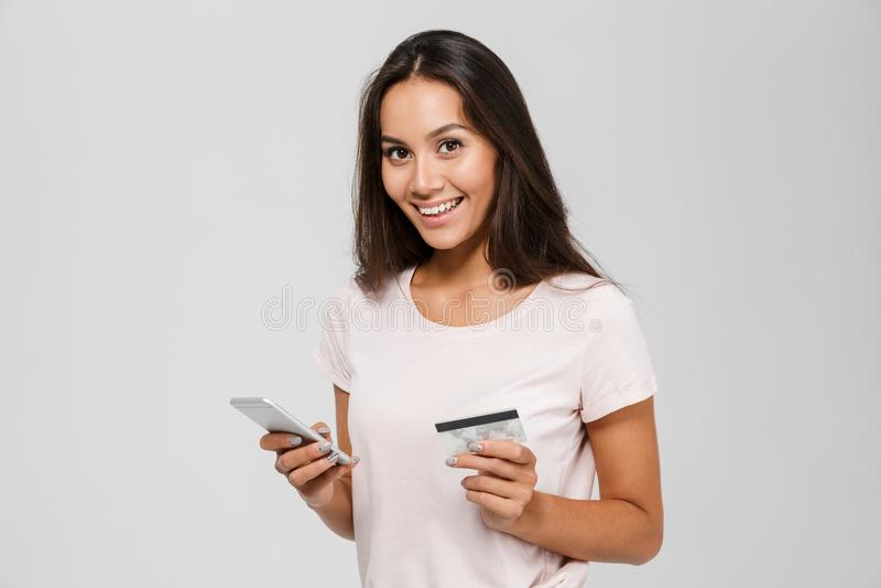 Retrato de uma mulher asiática feliz de sorriso que guarda o cartão de crédito fotos de stock