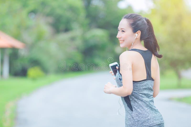 Retrato de uma mulher asiática nova que faz o exercício exterior no parque, foto de stock
