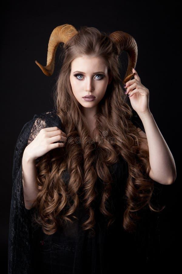 Retrato de uma mulher atrativa do demônio com chifres foto de stock