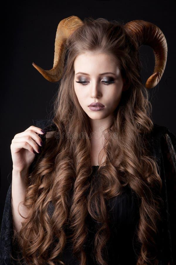 Retrato de uma mulher atrativa do demônio com chifres imagens de stock
