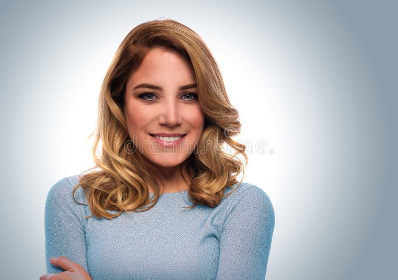 Retrato de uma mulher atrativa em um vestido azul imagens de stock