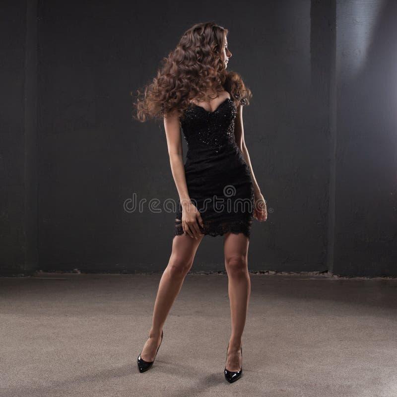 Retrato de uma mulher atrativa nova com cabelo encaracolado lindo morena nova no vestido preto pequeno imagem de stock