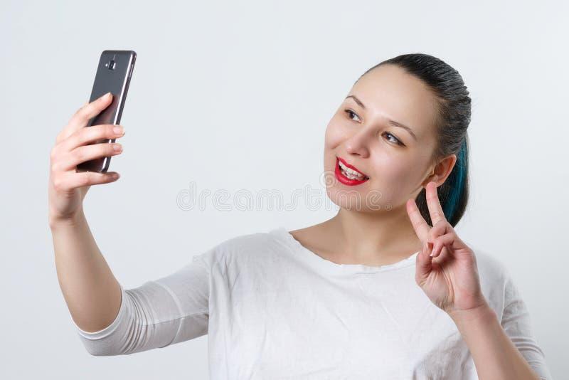 Retrato de uma mulher atrativa nova que faz a foto do selfie no smartphone em um branco imagens de stock royalty free