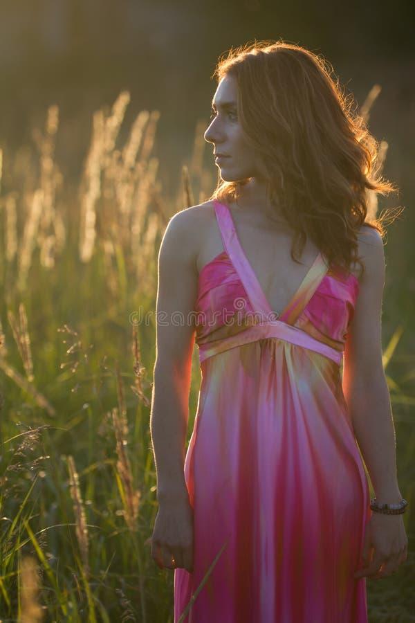 Retrato de uma mulher atrativa que levanta no prado do verão no por do sol imagem de stock royalty free