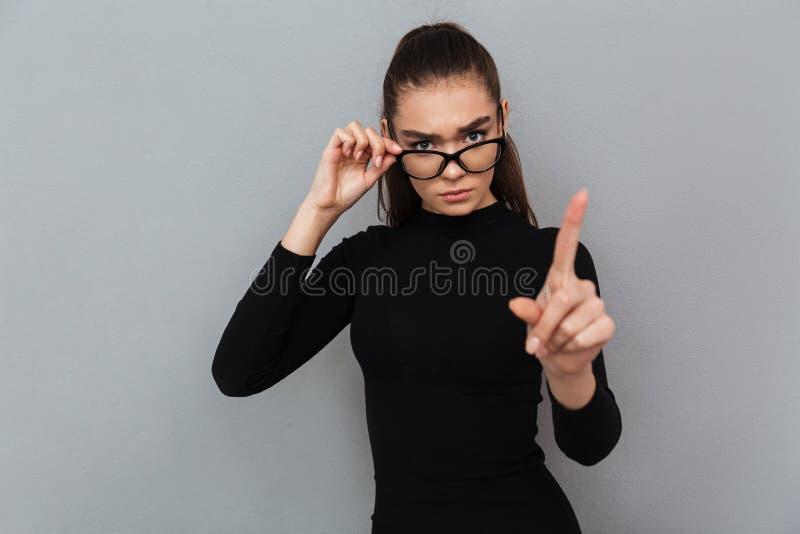 Retrato de uma mulher atrativa séria no vestido preto fotografia de stock
