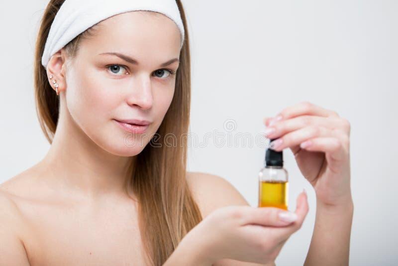 Retrato de uma mulher bonita com óleo facial nas mãos imagens de stock