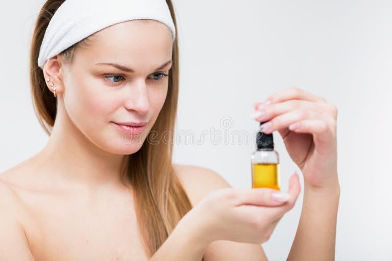 Retrato de uma mulher bonita com óleo facial nas mãos foto de stock