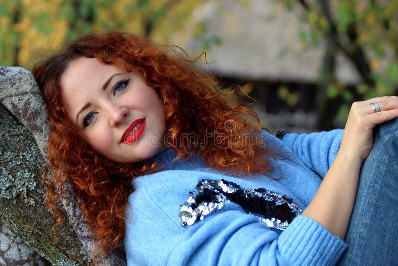 Retrato de uma mulher bonita com cabelo vermelho e um sorriso bonito que encontra-se em uma cobertura, propagação para fora em um fotos de stock royalty free