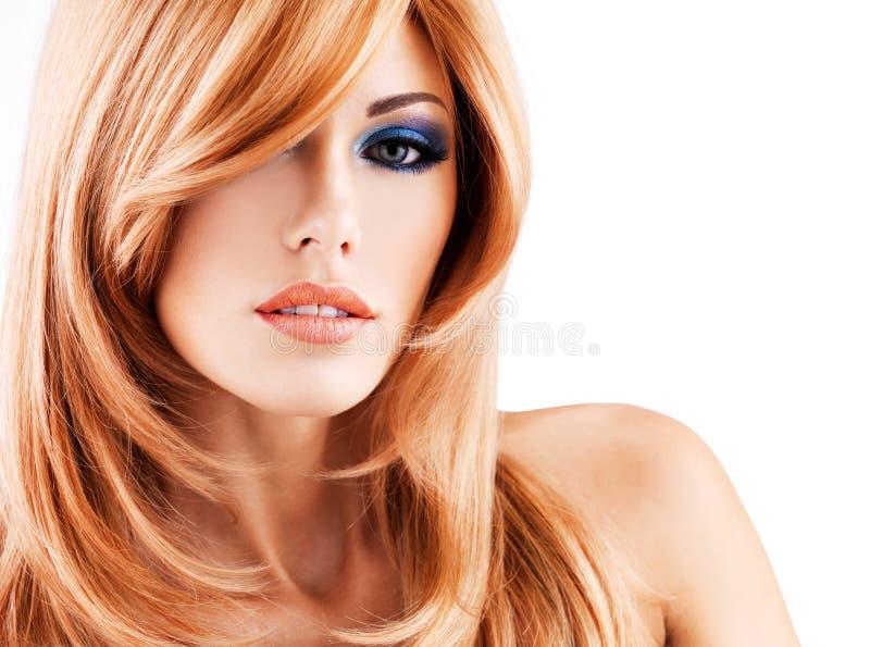 Retrato de uma mulher bonita com cabelos vermelhos longos e o makeu azul imagem de stock
