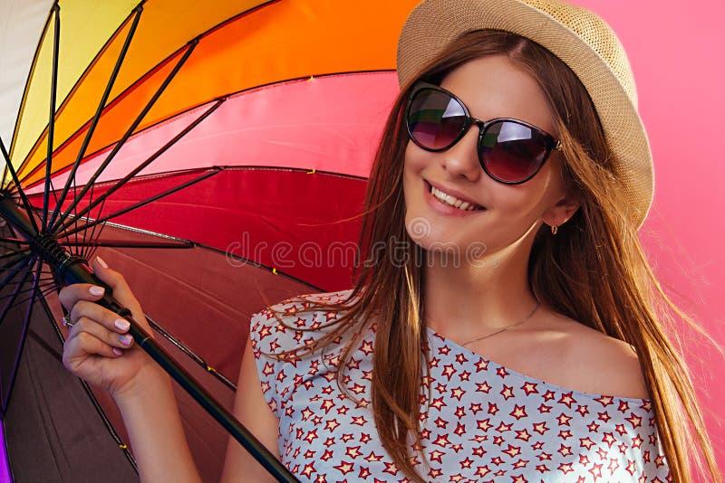Retrato de uma mulher bonita com os óculos de sol vestindo do guarda-chuva colorido foto de stock royalty free