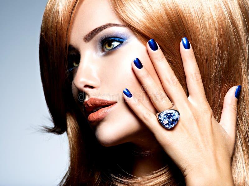 Retrato de uma mulher bonita com pregos azuis, composição azul foto de stock royalty free